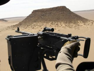A UH 60 Blackhawk Helicopter Crew Chief Holds an M240G Medium Machine Gun During a Flight Photographic Print by Stocktrek Images