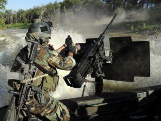 Special Warfare Combatant Craft Crewman Reloading an M2 Heavy Barrel .50 Caliber Machine Gun Photographic Print