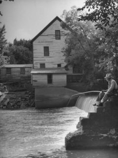 Man Fishing Beside a Waterfall and a 100 Year Old Mill Premium Photographic Print by Bob Landry